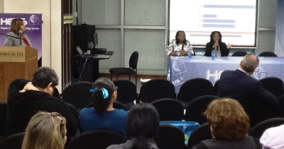 Moderator, Brenda Acevedo from Atenas College and the audience listening to Prof. Natasha Nurse and Prof. Myriam Cadet from Lehman College (CUNY) during the event at UNE.